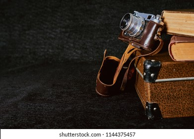 Old vintage retro suitcase, camera and books on dark coarse texture cloth. Nostalgia travel set