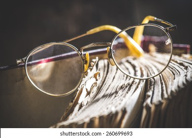 Old vintage round glasses and old book. Low light