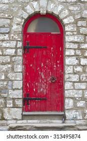 Old vintage rustic exterior red door detail on old brick building.