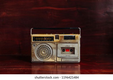 Old vintage rustic transistor radito with cassette recorder with dark wooden background