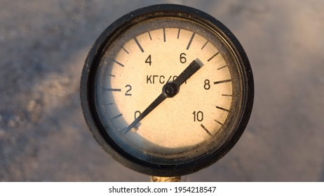 Old vintage rusty psi bar pressure measurement gauge installed on pneumatic equipment. Text in russian - kilogram-force.