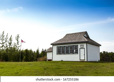 An old vintage school house with a Canadian flag in the yard
