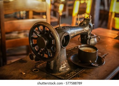 Old VIntage Sewing Machine with a Coffee Cup on a Village Table