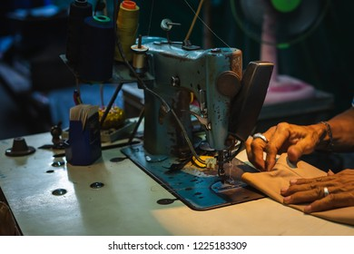 Old vintage Sewing machine and Hands of the tailor working on sewing machine at Bangkok street market . Selective focus