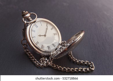 Old vintage silver pocket watch on gray stone surface, closeup with extremely shallow depth of field