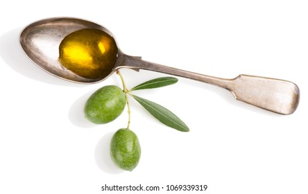 Old vintage spoon with olive oil and fresh green olives isolated on white background.