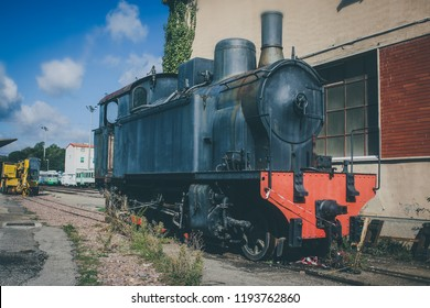An old vintage steam locomotive waiting in front of a shed in Macomer, Sardinia, hoping to recieve a bright new future as a museum locomotive