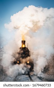 Old vintage steam train on the rail road. Steam, smoke covering the train. Retro steam train departs from the railway station