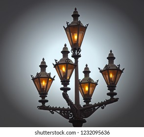 Old vintage street lamp with burning lamps against the sky.