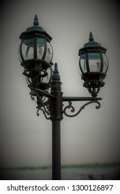 Old vintage street lamp on dark backgroud. Lantern in London/ England style with nature and sky in background. Obscure