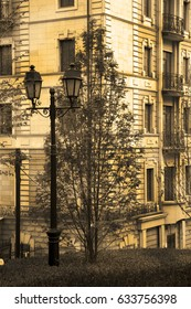 Old vintage street lamp in the style of the 18th century with two lampshades stands in a park next to a tree; In the background saw an old house with stucco on the facade; Photo in sepia style