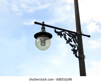 Old vintage street light against blue sky.