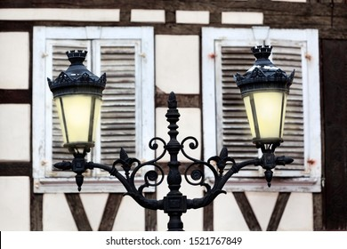 Old vintage streetlight in front of closed window shutters in Niederbronn les Bains in France