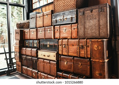 Old vintage suitcases and chests stacked in a heap