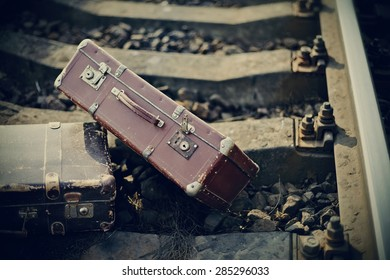 Old vintage suitcases are forgotten on railway rails.