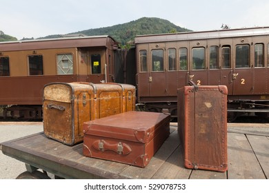 Old, vintage suitcases on railway platform with train in the background