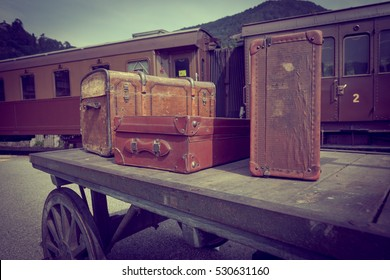 Old, vintage suitcases on railway platform with train in the background in vintage style