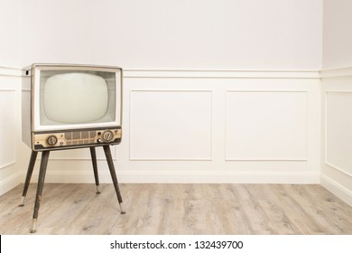 Old vintage television in the corner of cozy room, left hand space available for text or graphic