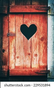 Old vintage toilet door with a heart shaped hole, filters applied