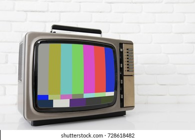 Old vintage TV with glitch screen over white brick wall background and copy space with add your text.