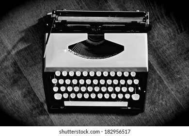 Old vintage typewriter  on wooden background, high contrast black and white photo