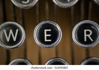 Old vintage typewriter on wooden desk. close up of black and white keys focusing on the letter E.