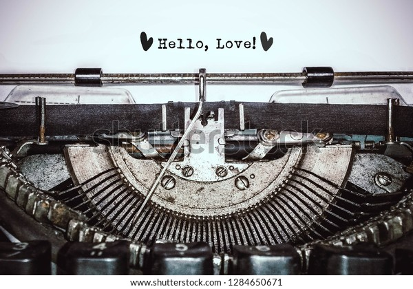 """Old vintage typewriter, retro machine with white sheet of paper and typed text """"Hello, Love!"""", copy space, close up"""