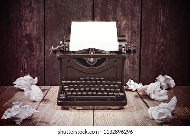 Old vintage typewriter and wadded up paper on a wooden background