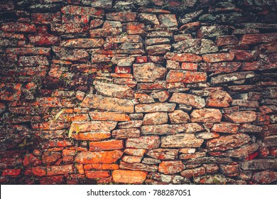 Old vintage wall in orange dark brown shades with occasional climbing plants. Uncommon ancient bricklaying. Ideal background for retro collages and illustrations.