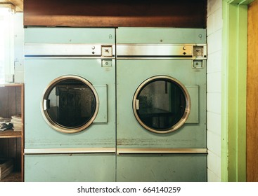 Old vintage washing machines from the sixties sit in a dirty run down laundry mat.  More of the laundry mat is reflected in the washer doors and a disheveled magazine rack sits in the sun.