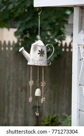 Old vintage watering can wind chimes in a garden