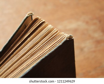 Old, vintage well read classic collectible hard cover novel. The book is situated in an semi open, upright standing position on a wood desk.