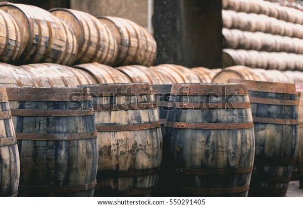 Old vintage whisky barrels filled of whiskey placed in order in small traditional distillery in Scotland