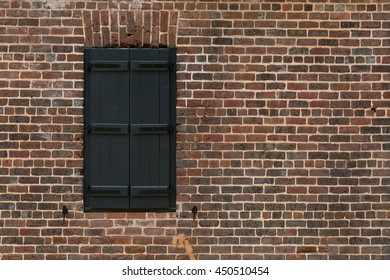 Old vintage window with black shutters on a red brick wall in darker tones