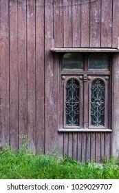 Old vintage window on a wooden house. brown background. Green grass at the bottom.