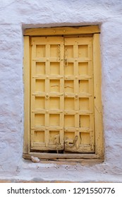 old vintage window painted in yellow on a purple wall
