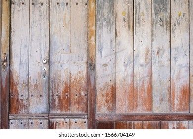 Old vintage wood front door with door knob, handle and key hole. Weathered wooden texture stained color shade. Surface coat already peel off. Background pattern concept.
