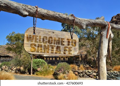 """old vintage wood signboard with text """" welcome to santa fe"""" hanging on a branch"""
