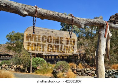 """old vintage wood signboard with text """" welcome to Fort Collins"""" hanging on a branch"""