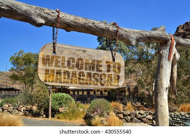 "old vintage wood signboard with text "" welcome to madagascar"" hanging on a branch"