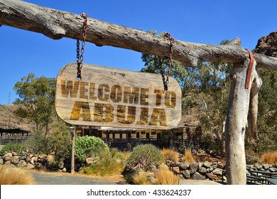 "old vintage wood signboard with text "" welcome to Abuja"" hanging on a branch"