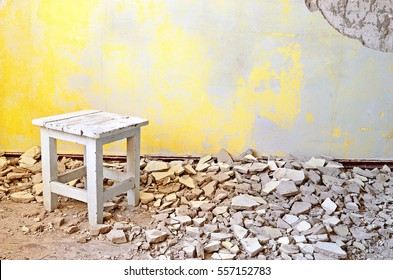 Old vintage wooden chair in an abandoned grunge room with cracked yellow cement mortar wall background. Grunge vintage interior. Old grungy cement brick wall with blank space for text.