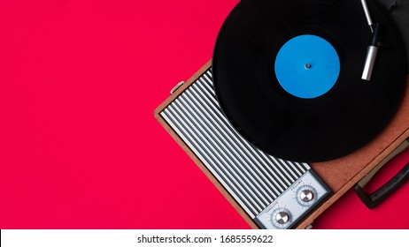 Old vinyl player and turnable on a red background. Entertainment 70s. Listen to music. Top view.