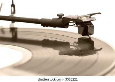 A old vinyl record album plays on a turntable. Sepia tones. Macro, shallow dof, focus on needle. From the 80s.