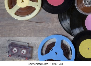Old vinyl records, audio tapes and reels of magnetic tape on the table