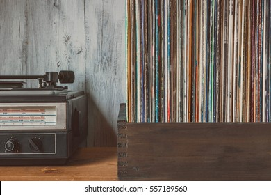 Old vinyl records in a box and the player standing on the table