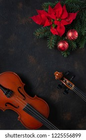 Old violin and fir-tree branches with Christmas decor and poinsettia.  Christmas and New Year's concept. Top view, close-up on dark concrete background.