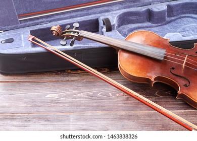 Old violin on wooden background. Aged viola, fiddle stick and velvet case. Classical musical instrument.