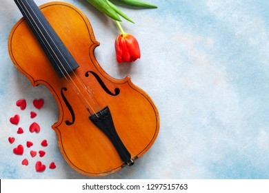 Old violin, red heart figurines and red tulip. Valentine day, 8 March concept. Top view, close-up on blue sky concrete background