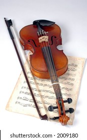 Old violin with vintage music sheet over white background